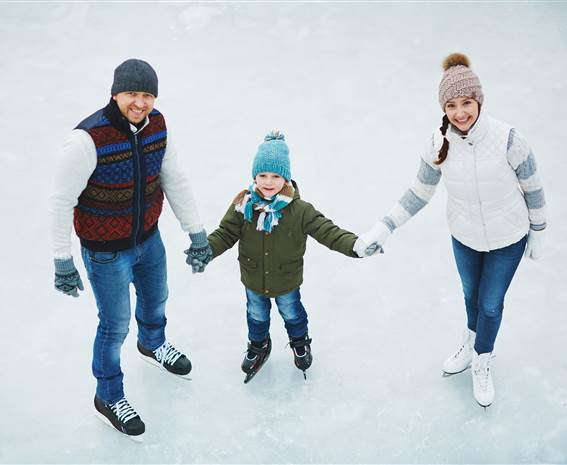 Family with skates on ice rink holding hands