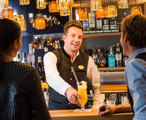 Waiter serves cocktail to hotel guests at the bar