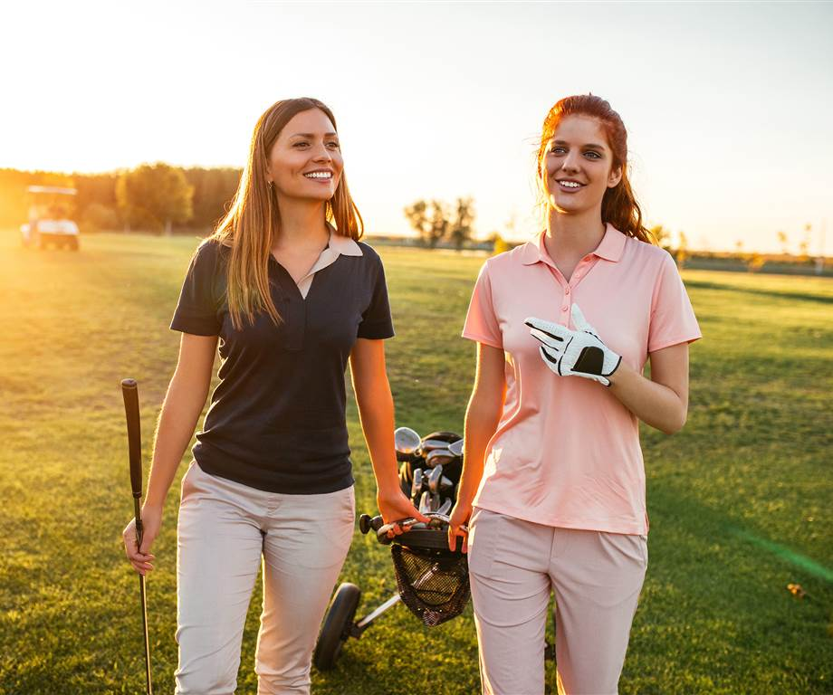 Two women pull golf bag on golf course