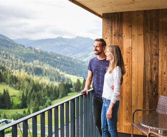 Couple stands on balcony and looks at nature
