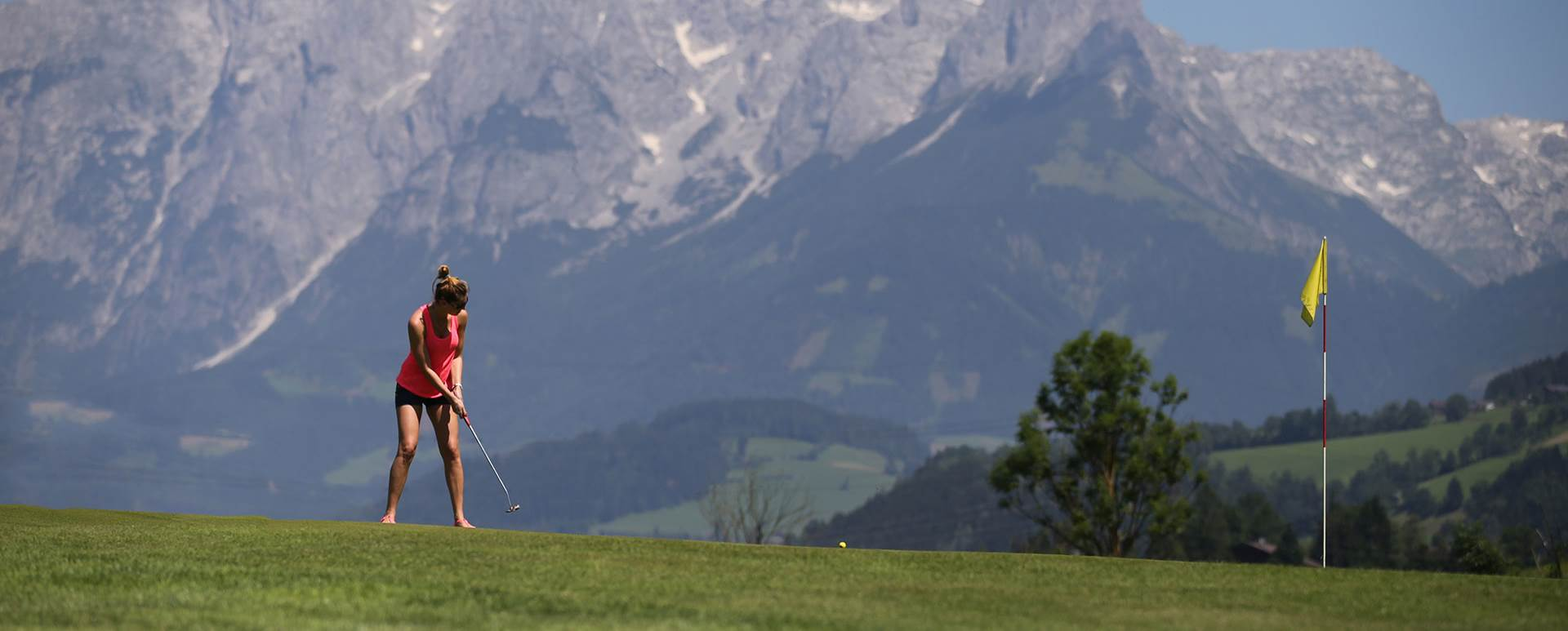 Woman plays golf with mountain panorama