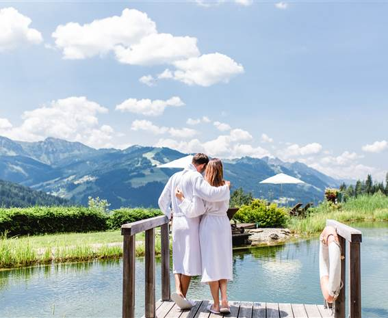 Couple in bathrobe stands on the jetty with a view of the swimming biotope