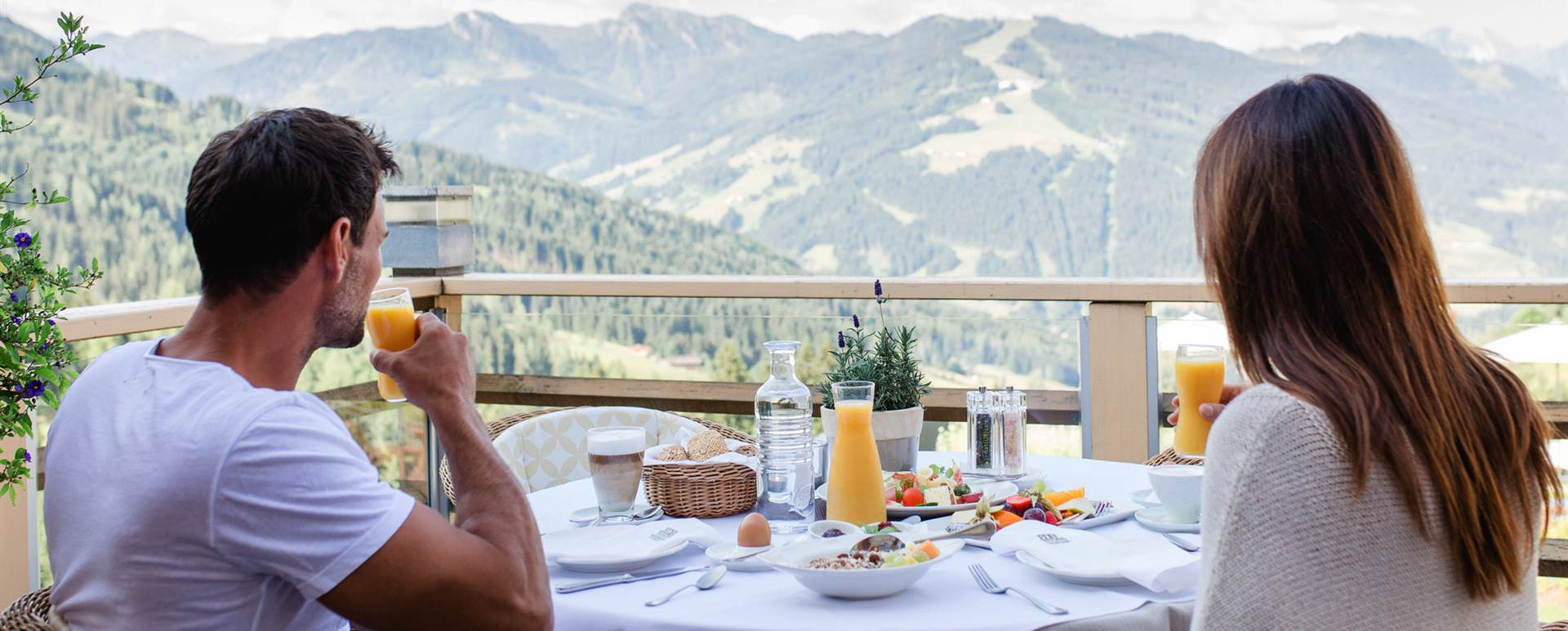 Couple having breakfast on the terrace with a view of the mountain panorama